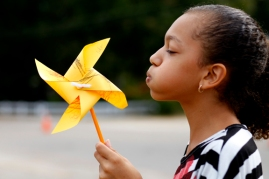 Fifth-grader Nia Steadwell tries to blow a pinwheel before planting it in the grass outside of Carthage Elementary School Sept. 20. Steadwell and her classmates planted 450 pinwheels made by students in pre-k through fifth grade in celebration of the International Day of Peace.